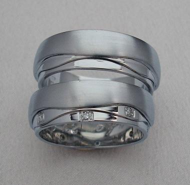 Veľmi netradičné svadobné obrúčky z bieleho zlata sú rozdelené nepravidelnými drážkami na tri nerovnako veľké časti. Najväčšia časť je matovaná, zvyšné dve majú lesklý povrch zdobený, v dámskej variante, vsadenými drobnými diamantmi.