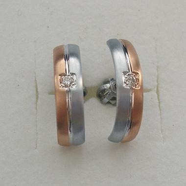 Náušnice z bieleho a červeného zlata do sady k svadobným prsteňom. Náušnice sú rozdelené drážkou na dve polovice podľa farby zlata, uprostred je zasadený drobný diamant.