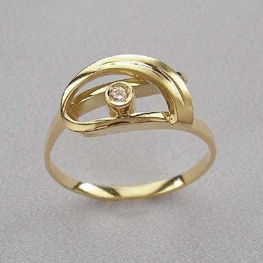 Prsteň netradičného tvaru zo žltého zlata zdobený menším vsadeným diamantom.